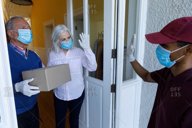 Delivery man wearing face mask delivering package to senior caucasian couple wearing face mask at ho