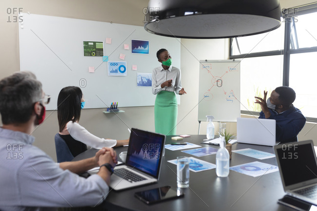 African american woman wearing face mask giving presentation to her diverse colleagues at modern off