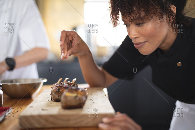 Female african american chef adding salt over grilled ribs on wooden board at restaurant kitchen