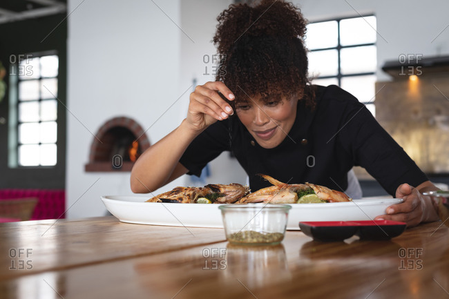 Female african american chef adding salt over roasted fish in food plate at restaurant kitchen