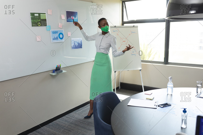 African american woman wearing face mask giving presentation in meeting room at modern office