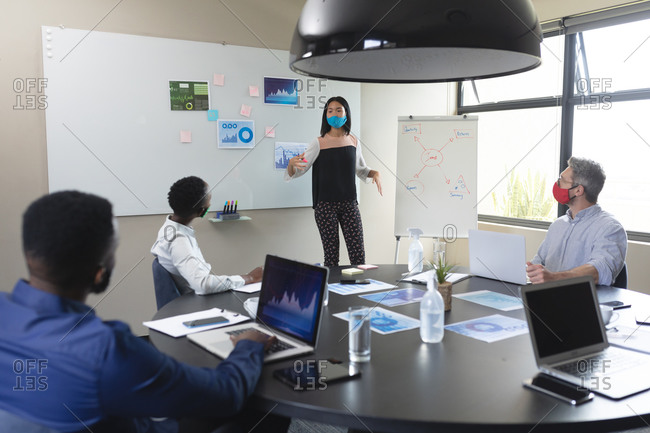 Asian woman wearing face mask giving presentation to her diverse colleagues at modern office