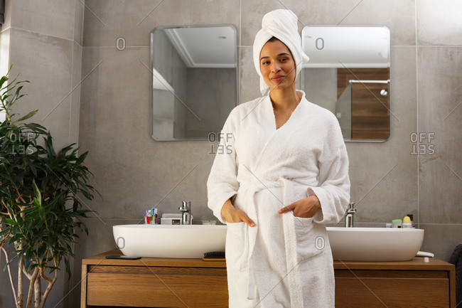 Portrait of smiling mixed race woman wearing bathrobe and towel on head standing in bathroom