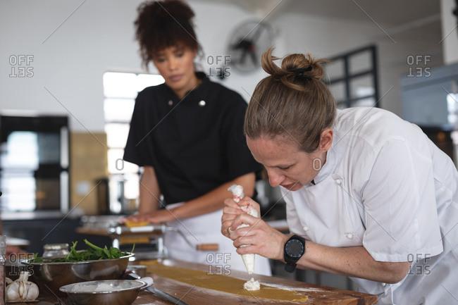 Female senior caucasian chef adding fillings over ravioli pasta sheet at restaurant kitchen