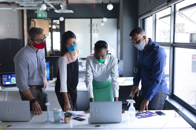 Diverse colleagues wearing face masks using laptop while working together at modern office