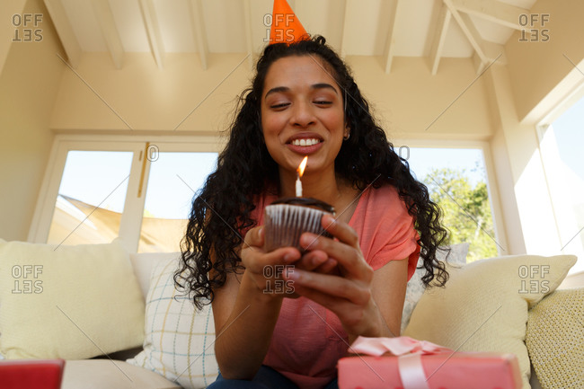 Mixed race woman celebrating birthday wearing party hat holding muffin with candle on it