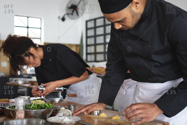 Male middle eastern chef cutting individual ravioli with stuffing at restaurant kitchen