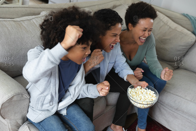 Mixed race lesbian couple and daughter sitting on couch watching tv and eating popcorn