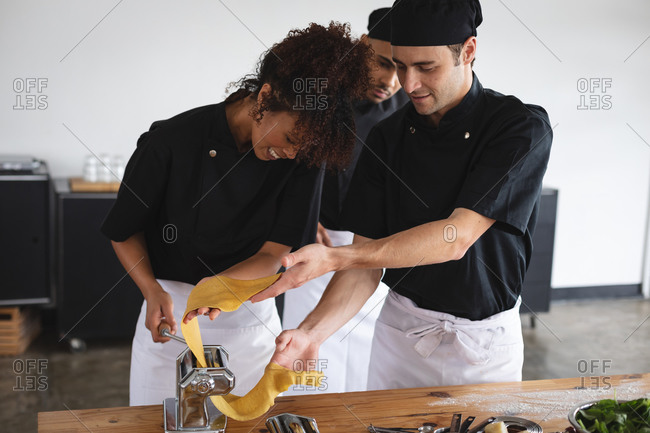 Diverse male and female chef processing pasta sheet in machine at restaurant kitchen