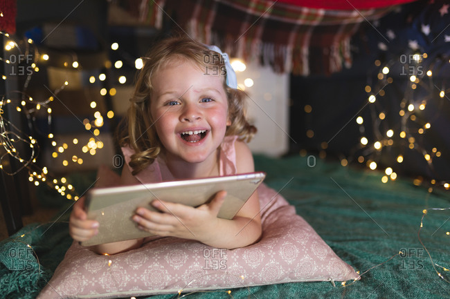 Caucasian girl lying on pillow and green blanket in bedroom using tablet and smiling