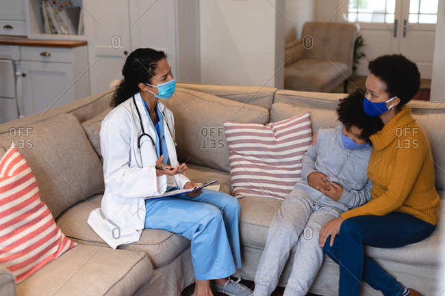 Mixed race mother and daughter talking to mixed race female doctor sitting on couch