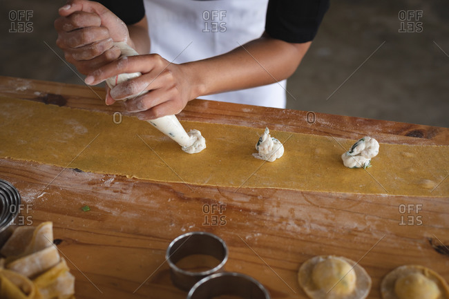 Mid section of chef adding fillings over ravioli pasta sheet at restaurant kitchen
