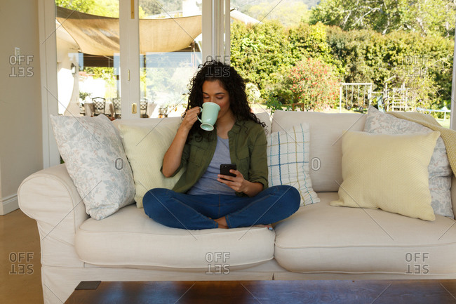 Mixed race woman drinking coffee using smartphone sitting on couch in living room