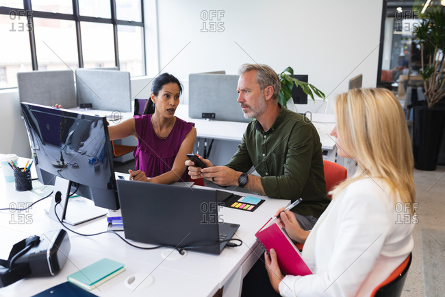 Diverse group working in creative office together, brainstorming, using computer