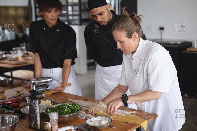 Senior caucasian female chef adding flour over pasta sheet at restaurant kitchen