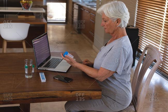Senior caucasian woman having video consultation using laptop holding medication