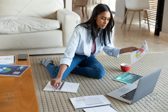 Mixed race woman sitting on floor using laptop holding documents working at home