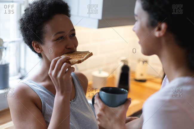 Happy mixed race lesbian couple having toast and coffee for breakfast in kitchen