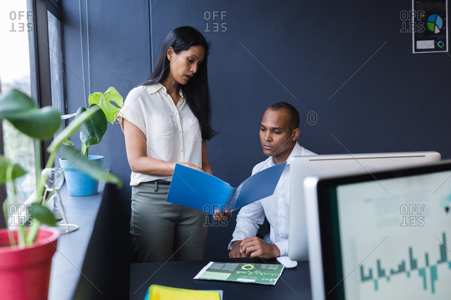 Mixed race man and woman working together in creative office, reading documents