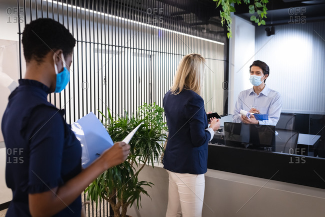 Diverse women wearing masks queuing to reception, receptionist holding clipboard