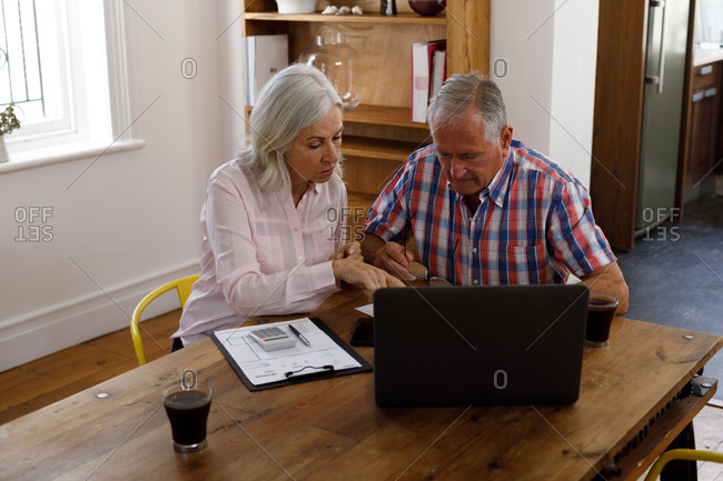 Stressed senior caucasian couple using laptop and calculating finances at home