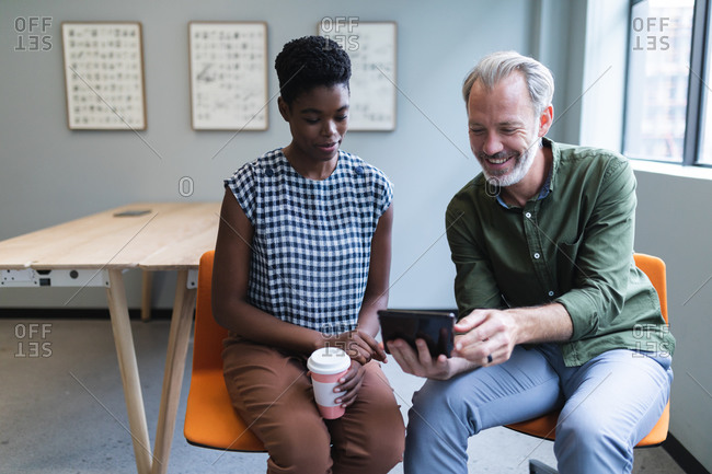 Diverse man and woman drinking coffee using digital tablet in creative office