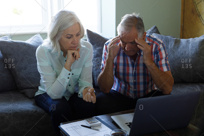 Stressed senior caucasian couple using laptop and calculating bills at home