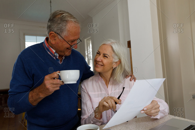 Happy senior caucasian couple with coffee cup calculating finances at home