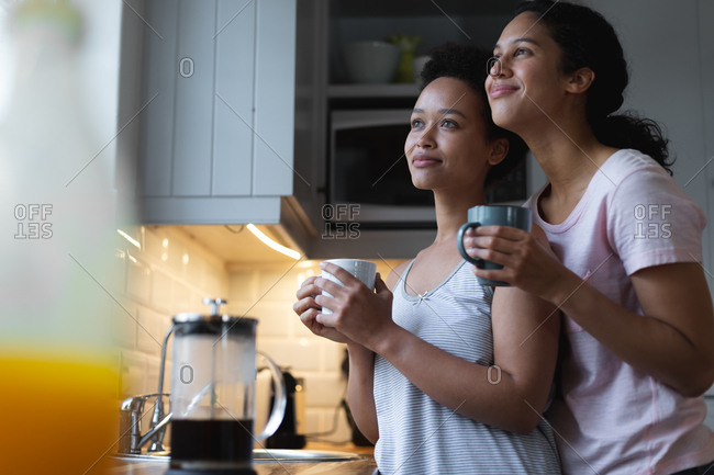 Smiling mixed race lesbian couple drinking coffee and embracing in kitchen