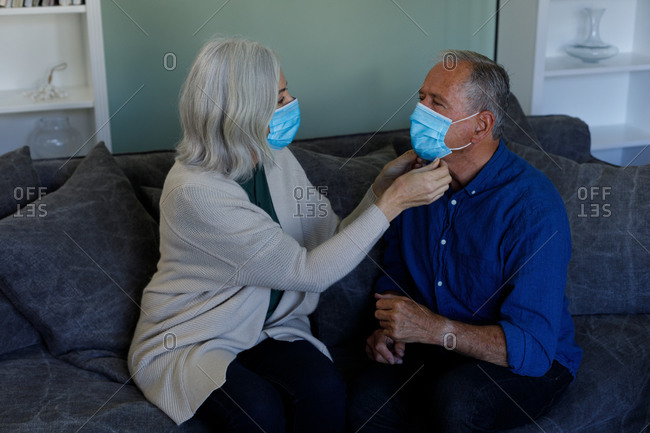 Senior woman wearing face mask adjusting face mask of her husband at home