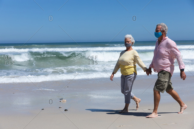 Senior caucasian couple wearing face masks walking on beach holding hands