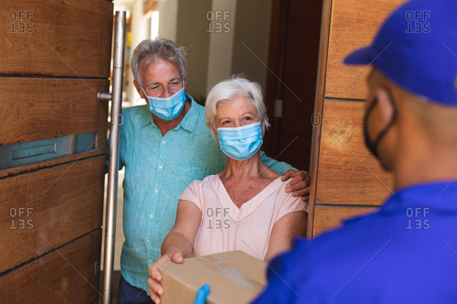 Senior caucasian couple wearing face masks receiving parcel from courier