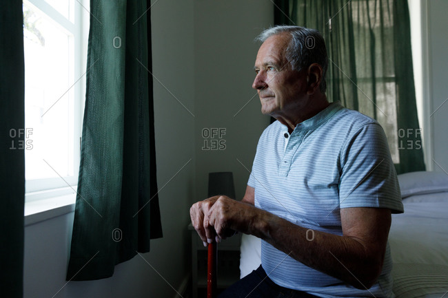 Senior caucasian man holding walking stick looking out of window at home