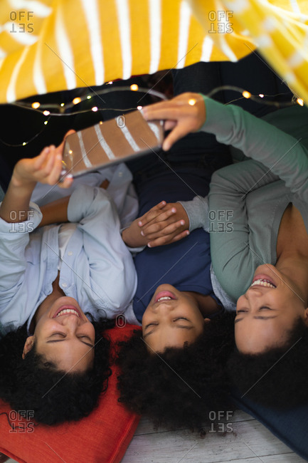 Happy mixed race lesbian couple and daughter lying down using smartphone