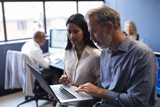 Diverse man and woman working together in creative office, using laptop