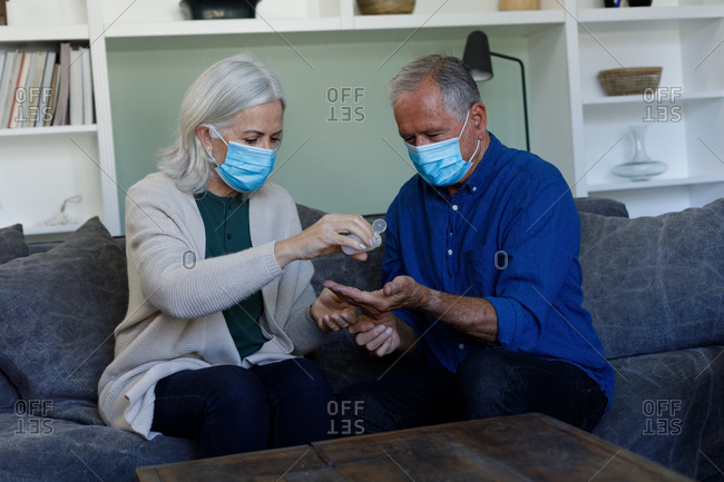 Senior caucasian couple wearing face masks using hand sanitizer at home