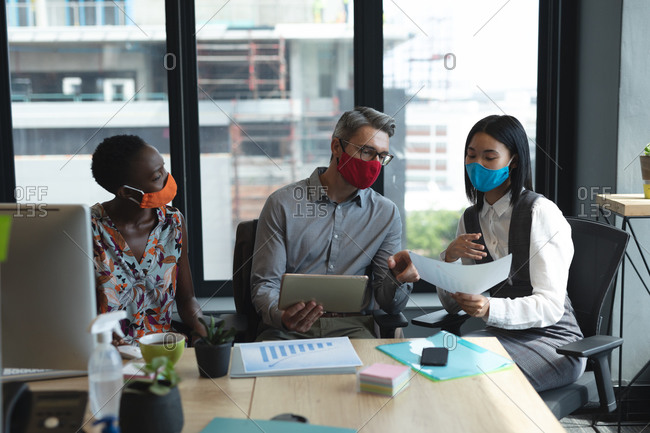 Diverse colleagues wearing face masks working together at modern office