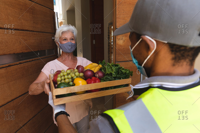 Senior caucasian woman wearing face mask receiving fruit crate delivery