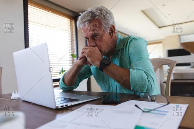 Worried senior caucasian man sitting at table using laptop paying bills