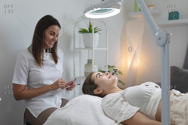 Caucasian woman lying back while beautician smiles and does her makeup