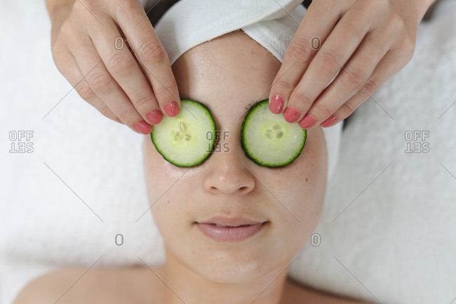 Caucasian woman lying back while beautician puts cucumbers on her face