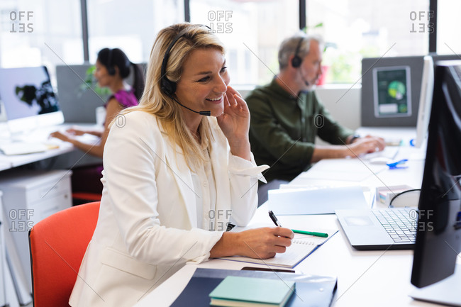 Caucasian woman wearing phone headset in modern office, using computer
