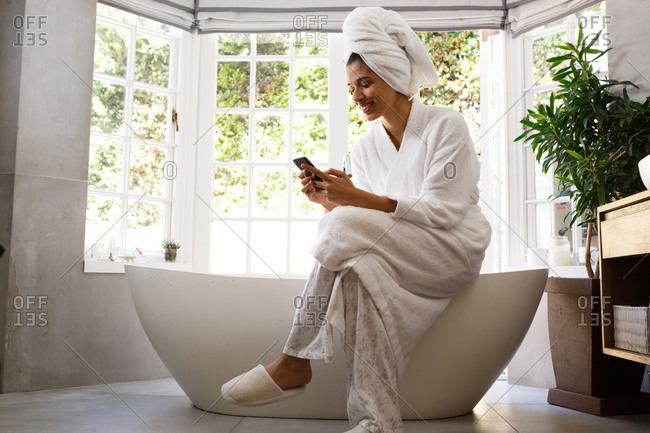 Mixed race woman wearing bathrobe sitting on bathtub using smartphone