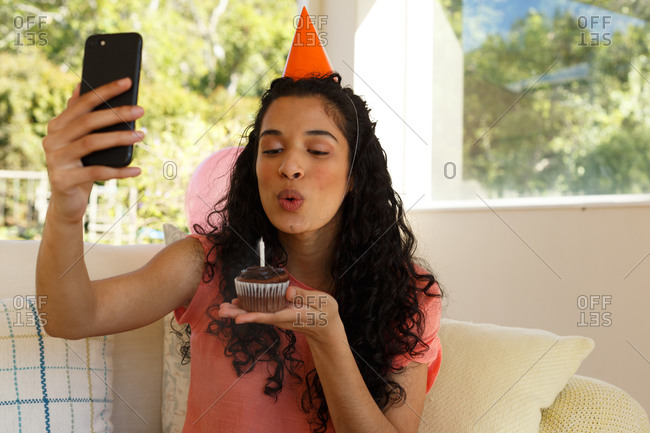 Mixed race woman celebrating birthday having video chat on smartphone