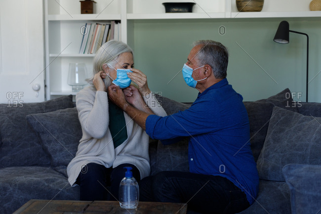 Senior man wearing face mask adjusting face mask of his wife at home