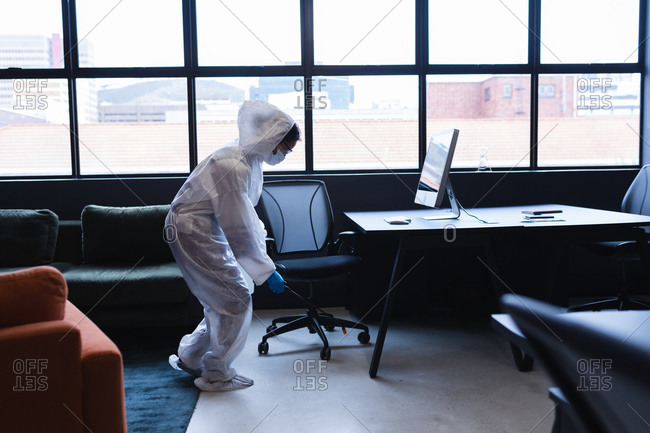 Health worker in protective clothing spraying disinfectant in office