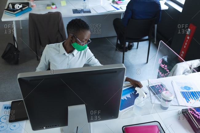 African american woman wearing face mask reading documents in office