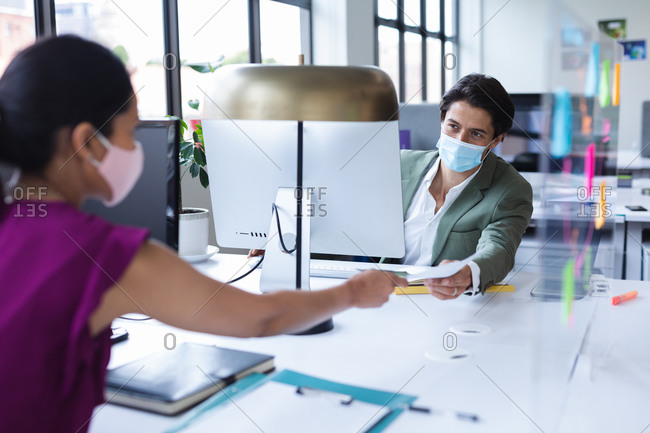 Diverse man and woman wearing face masks passing documents in office