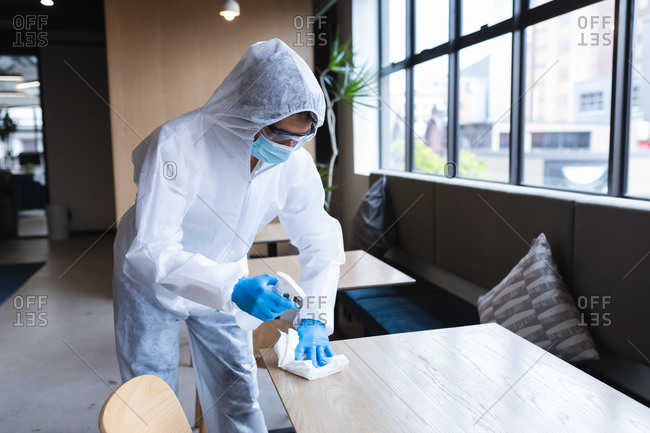 Health worker in protective clothing spraying disinfectant on table