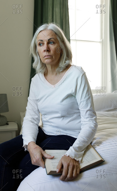 Stressed senior caucasian woman holding book sitting on bed at home